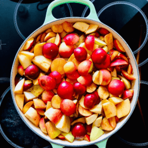 Overhead photograph of a pot of uncooked sliced crab apples sat on a hob