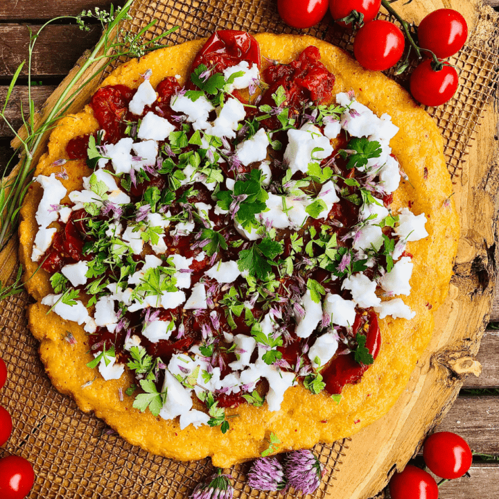 Overhead photograph of baked polenta topped with confit tomatoes and feta.