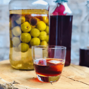 Glass of umeshu plum wine, with a jar of greegages steeping in vodka and a bottle of umeshu sitting in the background.